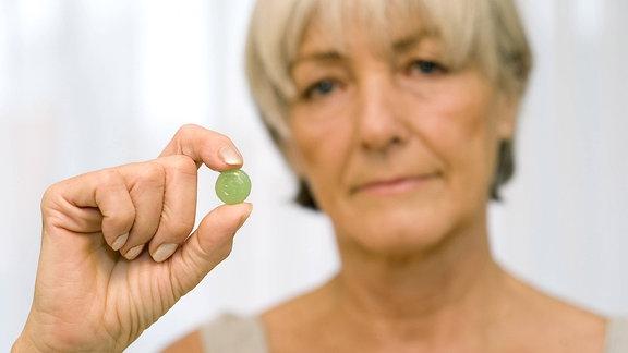 Frau in den Wechseljahren mit Tablette
