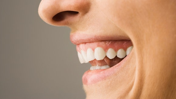 ein lächelnder Mund mit weißen Zähnen von der Seite.