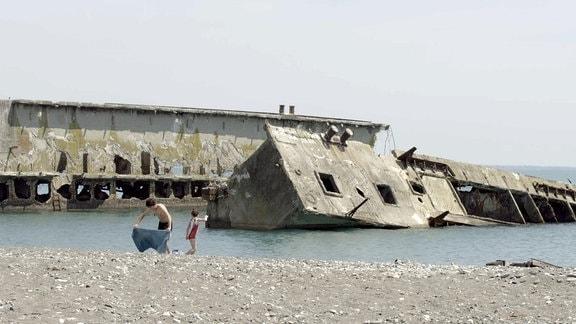 Kinder spielen am Strand im Hintergrund Hausbootwrack, das aus dem Wasser ragt