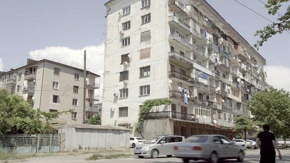 Wohnblock mit fahrenden Autos davor