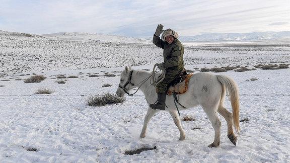 Mann reitet auf einem Pferd durch eine Winterlandschaft.