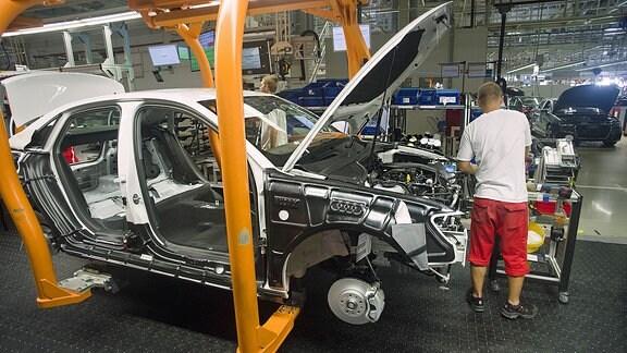 Ein Arbeiter montiert an einer Autokarosserie.