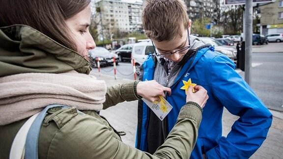 Zur Erinnerung an den Ghetto-Aufstand werden in Warschau Osterglocken aus Papier an Passanten verteilt.