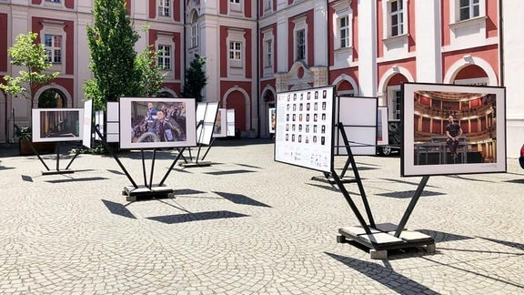 Ausstelungsstellwände mit Fotos auf einem historsichen Marktplatz.
