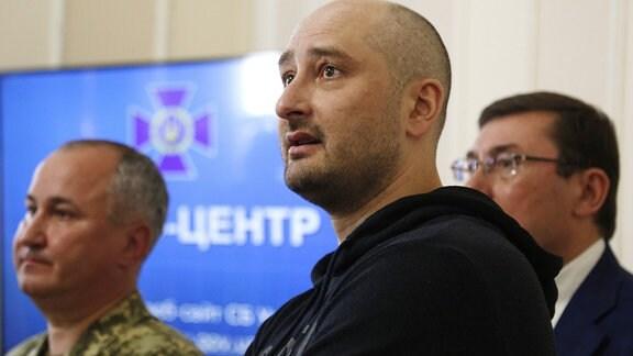Der russische Journalist Arkadi Babtschenko (M), Wassili Grizak (l), Chef des ukrainischen Geheimdienstes SBU, und Jurij Luzenko, ukrainischer Generalstaatsanwalt (r) reden auf einer Pressekonferenz mit Medienvertretern. Der angebliche Mord an Babtschenko sei eine über Monate vorbereitete Aktion gewesen, um Anschlagspläne des russischen Geheimdienstes zu enttarnen, sagte Grizak. Babtschenko erschien am Mittwoch lebendig und unverletzt bei einer Pressekonferenz des SBU