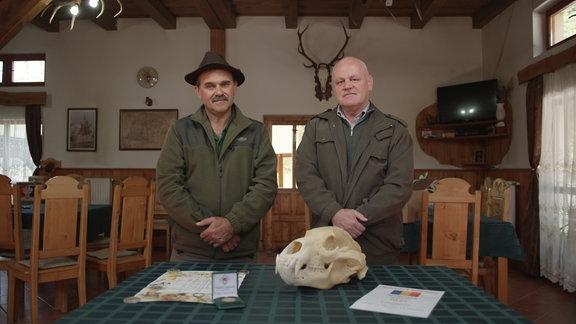 zwei Jäger in Jagdhütte vor Bärenschädel
