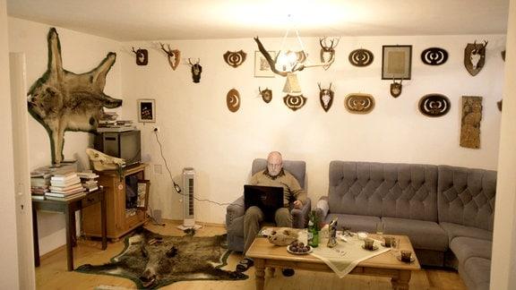 Jäger Benke sitzt in seinem Wohnzimmersessel umgeben von vielen Jagdtrophäen an der Wand