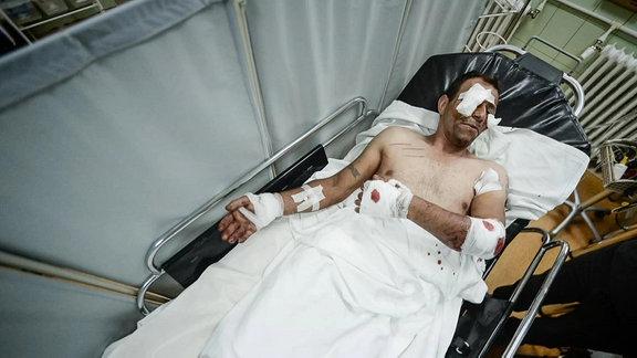 Patient liegt mit Kopfverletzungen auf Trage