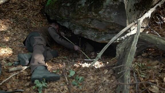 Jäger sucht liegend unter Felsvorsprung nach Eingang von Bärenhöhle