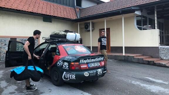 Zwei Männer laden Taschen aus Auto