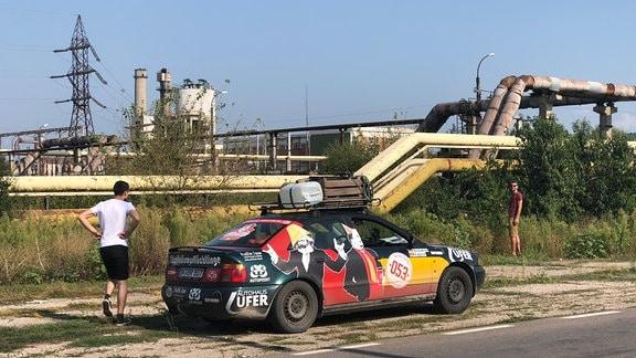 Audi A4 am Straßenrand vor Industrieanlage