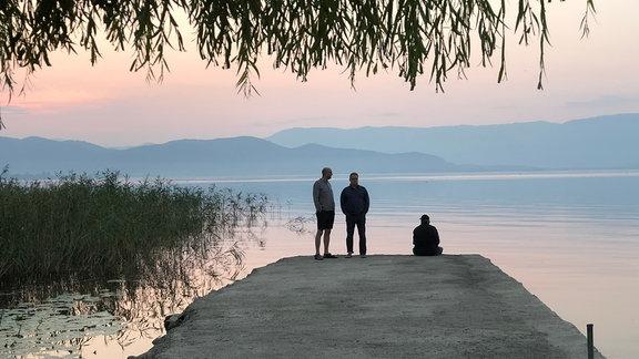 Morgenrot am Ufer des Ohridsee, drei Männer am Bootssteeg