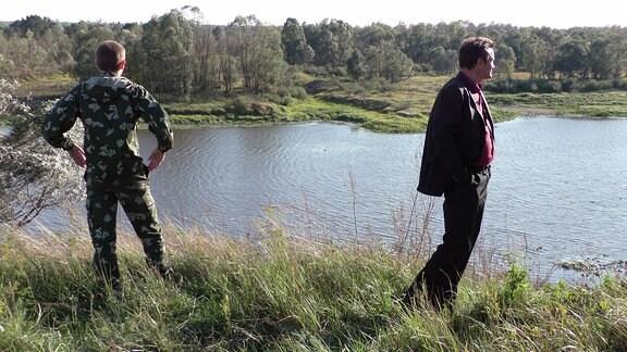 Zwei Männer stehen vor einem Fluß der die weißrussisch-ukrainische Grenze markiert.
