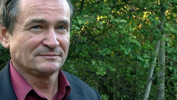 Ein Mann steht vor einer grünen Hecke und schaut Richtung Kamera. Nikolaj Woronetzki.