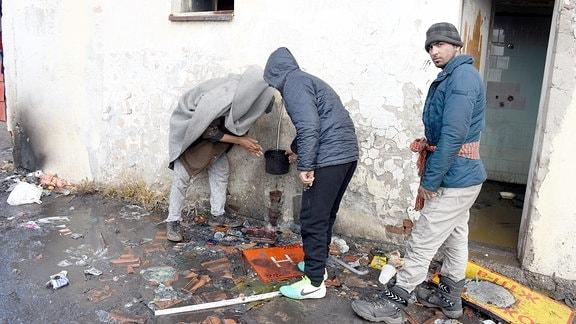 Belgrad, Flüchtlingslager: Junge Männer an Wasserleitung