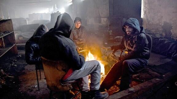 Flüchtlinge wärmen sich an Feuer im Flüchtlingslager Belgrad