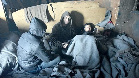 Junge Flüchtlinge unter Decken in Lagerhalle