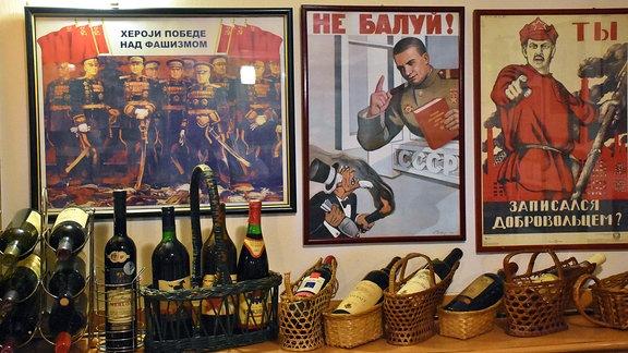 Bilder hängen an einer Wand. Weinflaschen stehen auf einem Regal.