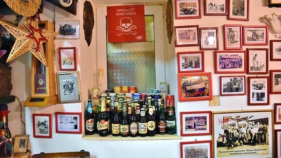 Bilder hängen an einer Wand. Bierflaschen stehen vor einem Fenster.