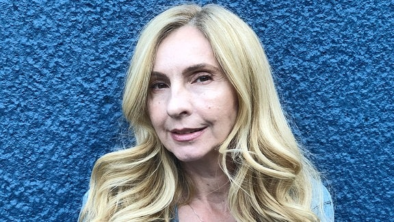 Blonde Frau in Jeansjacke vor einer blauen Wand.