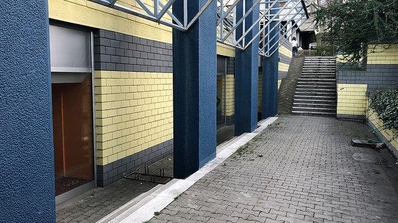 Blick auf einen Kellereingang in einem gelben Wohnhaus. Im Hintergrund einer Treppe.