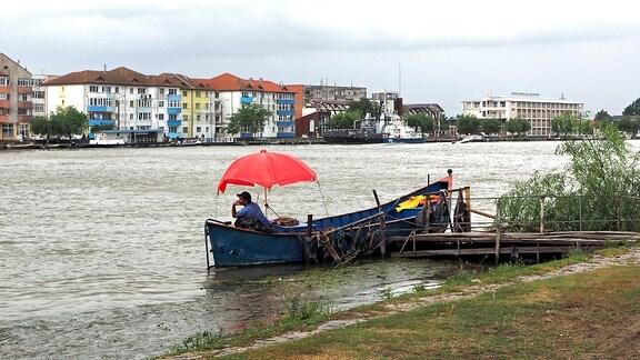 Angler auf dem Sulina Kanal vor der Skyline der Stadt.