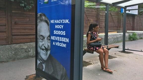 Schwarze Frau sitzt sn Budapester Bushaltestelle, an der Anti-Soros-Plakate hängen.