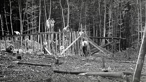 Die erste Baracke wird noch vor der Ankunft der Häftlinge von SS-Angehörigen gebaut. Den größten Teil des Lagers müssen die Inhaftierten aber danach selbst bauen.