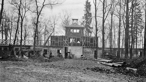 Im November 1937 ist das später bekannt gewordene Torgebäude im Rohbau fertig. Die Häftlinge müssen oft 14-16 Stunden am Tag schuften.