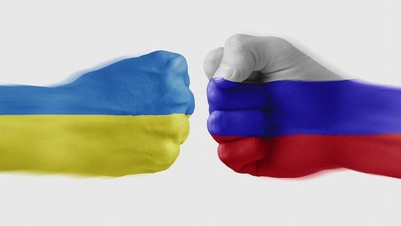 Zwei Fäuste, eine in den ukrainischen und eine in den russischen Nationalfarben