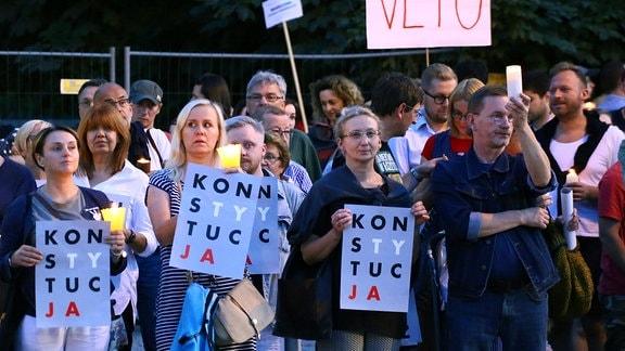 Demonstranten gegen eine umstrittene Justizreform versammeln sich am 22.07.2017 in Warschau (Polen) am Krasi_ski-Platz vor dem Obersten Gericht und halten angezündete Kerzen und Plakate (l) mit dem Schriftzug «Verfassung» hoch.