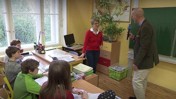 Ein Mann mit Mikrofon befragt eine Lehrerin