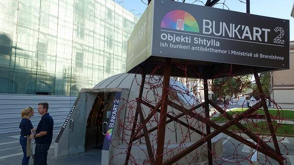 Zwei Besucher vor dem Eingang des unterirdischen Museums Bunk'art 2 in Tirana, Albanien.