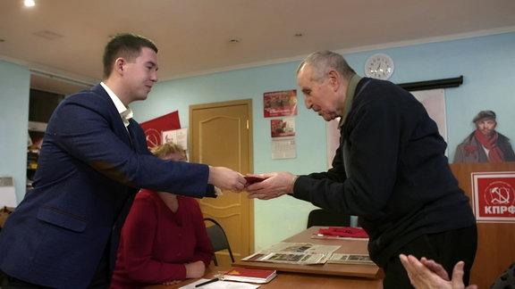 Altkommunist Walentin Karpumenko bekommt von Jongkommunist Iwan Zhangli einen Orden überreicht