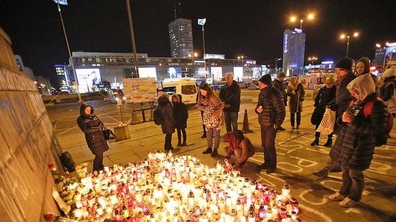 Menschen legen Kerzen im Zentrum Warschaus nieder, im Gedenken an Peter S., der sich dort Mitte Oktober selbst verbrannt hat