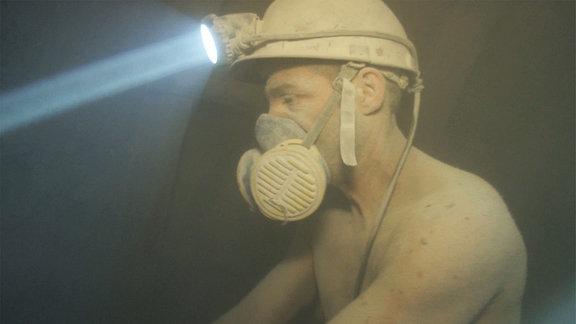 Ein Bergmann mit nacktem Oberkörper und Atemmaske bedient enen Presslufthammer und ist von Steinstaub umhüllt