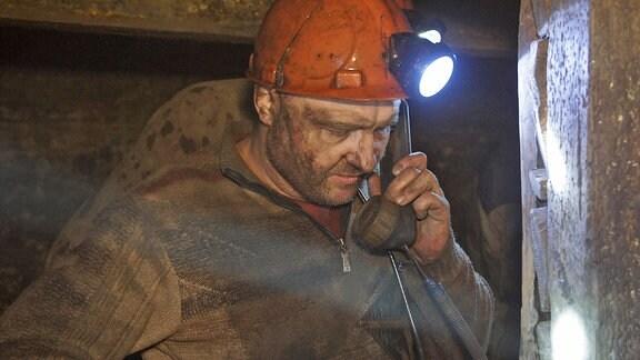 Ein Bergmann mit rotem Helm in der Grube am Telefon