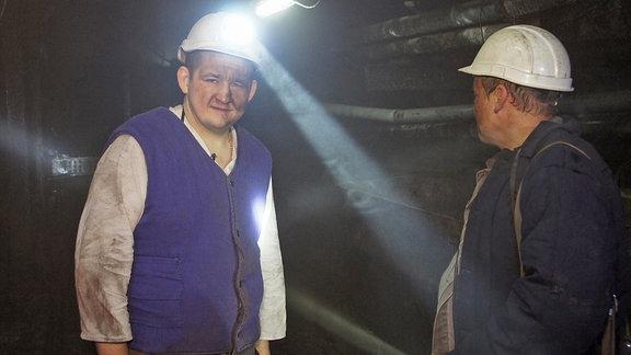 Bergleute mit eingeschalteten Helmlampen untertage