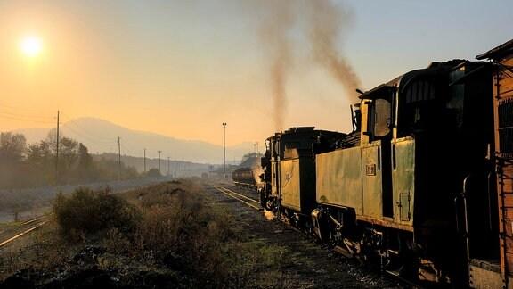 Abendstimmung im Endbahnhof Turija, wo ein Leerwagenzug mit gelich zwei Dampfloks an der Spitze angekommen ist.