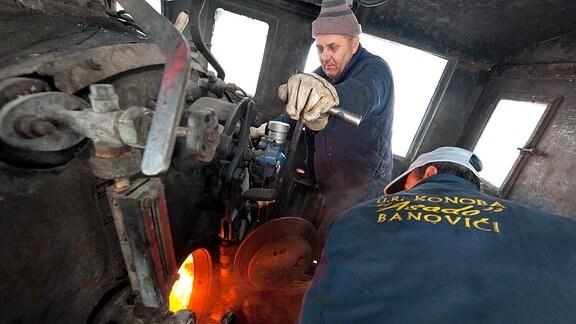 Teamarbeit zwischen Lokführer und Heizer auf dem Führerstand  der Dampflok.