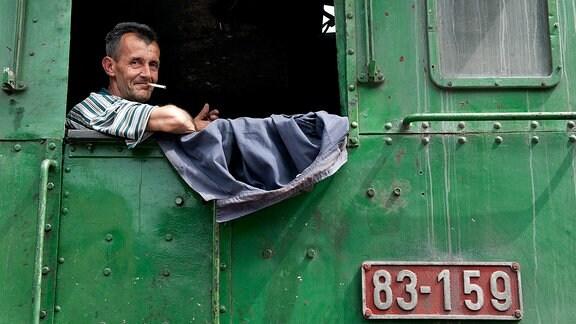 Zufrieden rauchender Lokführer auf der im Verschub eingesetzten Dampflok 83-159