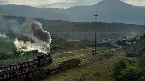 Ein Leerwagenzug ist in Turija dem Endpunkt der Strecke, angekommen. Im Hintergrund erkennt man den Ladebunker für die Eisenbahnwagen.