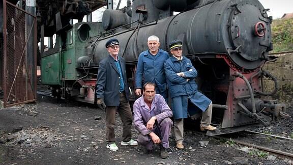 Lokführer, Heizer, Zugchef und Rangierarbeiter vor ihrer Dampflok der Baureihe 83.