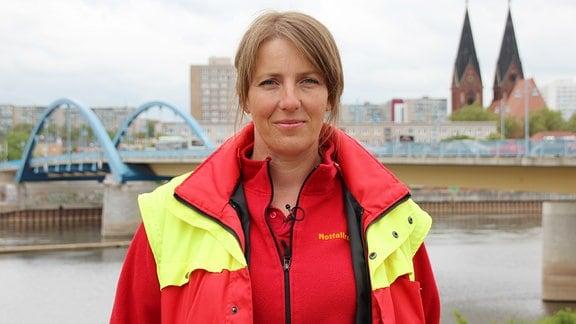 Blonde Frau in rot-gelben Jacke.