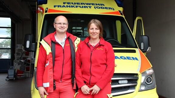 Ein Mann und eine Frau in rot-gelben Jacken vor einem gelben Rettungswagen.