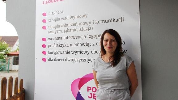 Eine junge Frau mit dunklen langen Haaren lehnt an einer Hauswand.