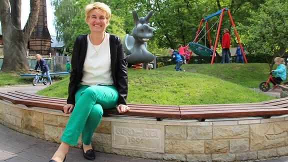 Eine blonde Frau sitzt auf einer Bank an einem Kinderspielplatz.