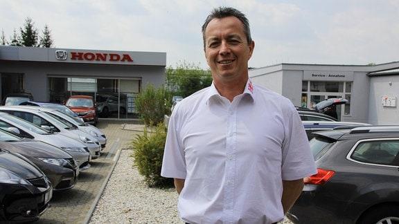 Ein Mann steht auf dem Parkplatz eines Honda-Autohauses.
