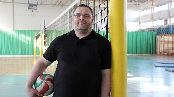 Ein Mann lehnt in einer Sporthalle an einem Pfosten. Unter seinem rechten Arm klemmt ein Ball.