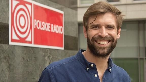 Mann mit lächelnd vor einem Haus. An der Wand ein Schild mit der Aufschrift: Polskie Radio.